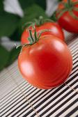 Tomatoes on a bamboo napkin — Stock Photo