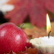 Burning candle with a red apple — Stock fotografie