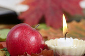 Burning candle with a red apple — Stock Photo
