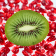 Cut fruit kiwi against garnet grains — Stock Photo #2144745