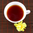 Cup of tewith yellow flower — Stock Photo #2144977