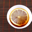 Cup of tewith lemon on bamboo napkin — Stock Photo #2144995