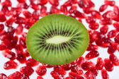 The cut fruit kiwi against garnet grains — Stock Photo