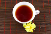 Cup of tea with a yellow flower — Stock Photo