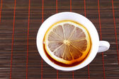 Cup of tea with a lemon on bamboo napkin — Stock Photo