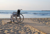 Wheelchair on sandy seacoast. The summer evening. — Stock Photo