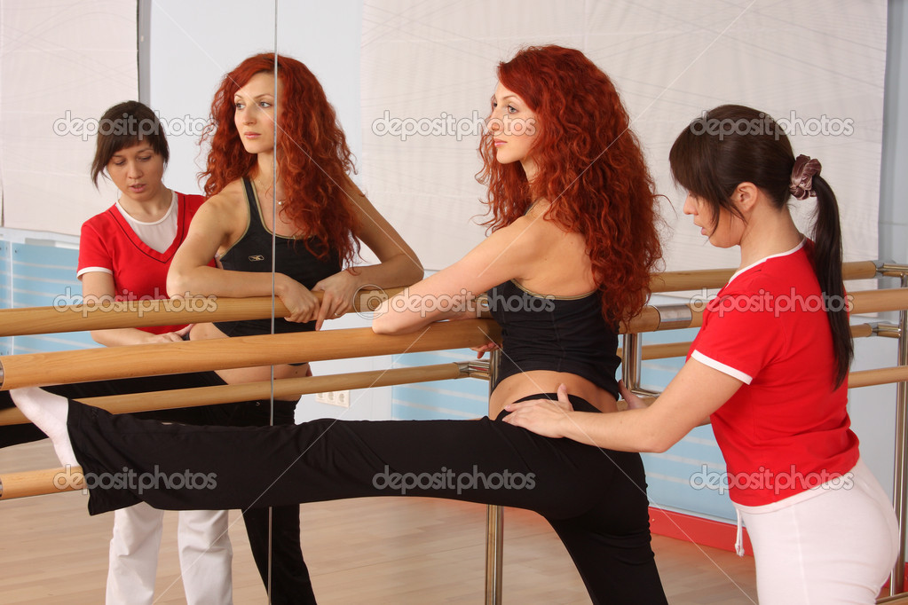 The pregnant woman with the instructor is engaged in gymnastics in a sports hall — Stock Photo #1533157