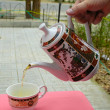 Pouring green tea in a teacup - Stock Photo