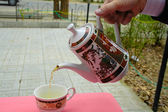 Pouring green tea in a teacup — Stock Photo
