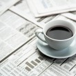 Foto Stock: Coffee over newspaper
