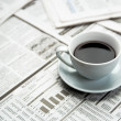 Coffee over newspaper — Stok fotoğraf