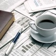 图库照片: Cup of coffee on newspaper