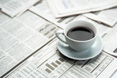 Coffee over newspaper — Photo