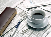 Cup of coffee on the newspaper — Stok fotoğraf