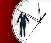 Biznesmen wisi na strzałce zegara — Zdjęcie stockowe
