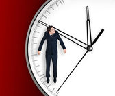 Businessman hangs on an arrow of clock — Стоковое фото