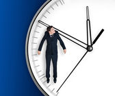 Businessman hangs on an arrow of clock — Zdjęcie stockowe