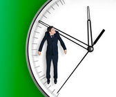 Businessman hangs on an arrow of clock — Stockfoto