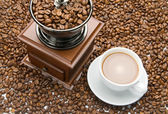 Old coffee grinder and a cup of coffee — Stock Photo