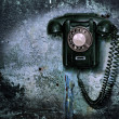 图库照片: Old phone on destroyed wall