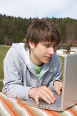 Teenager outside with laptop — Stock Photo