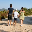 Happy family walking on the beach — Stock Photo