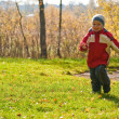 Stock Photo: Little boy running in autumn forest