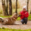 Stock Photo: Little girl playing with her dog