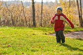 Little boy running in autumn forest — Stock Photo