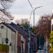 Wind turbine and small town in Germany - Stock Photo
