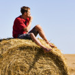 Stock Photo: Sitting on straw roll