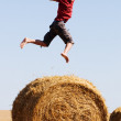Jumping on straw roll — Stock Photo