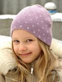 Happy little girl in a lilac hat. — Stock Photo