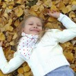 Little girl lying on autumn leaves — Stock Photo