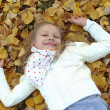 Royalty-Free Stock Photo: Little girl lying on autumn leaves