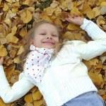 Little girl lying on autumn leaves — Stock Photo
