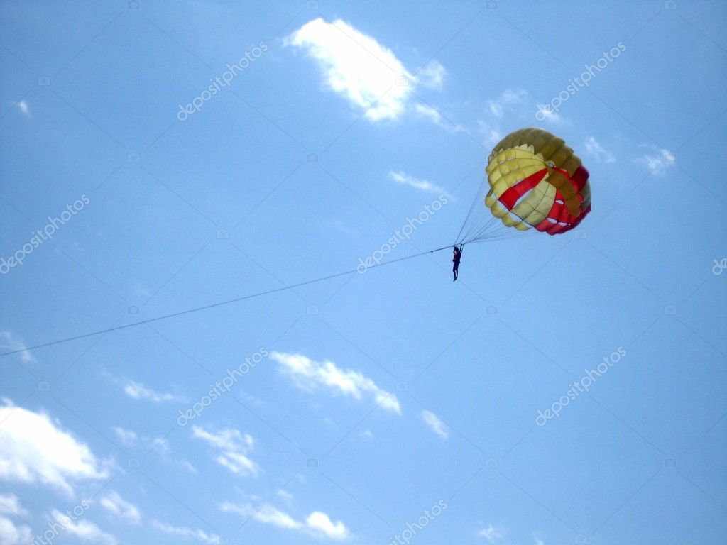 Sky Diver. Man with colourful parachute against blue sky. Paragliding In The Sky. Parachutist flying through blue and cloudy sky. — Стоковая фотография #1129364