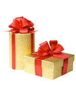 Two gold gift boxes with red ribbons — Stock Photo