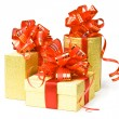 Stock Photo: Gold gift boxes with red ribbons and bow