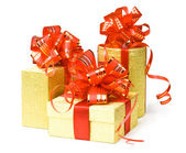 Gold gift boxes with red ribbons and bow — Stock Photo