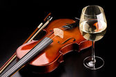 Violin and a glass of wine on the table — Stock Photo