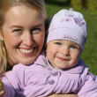 Mother holding daughter outdoors smiling — Stock Photo