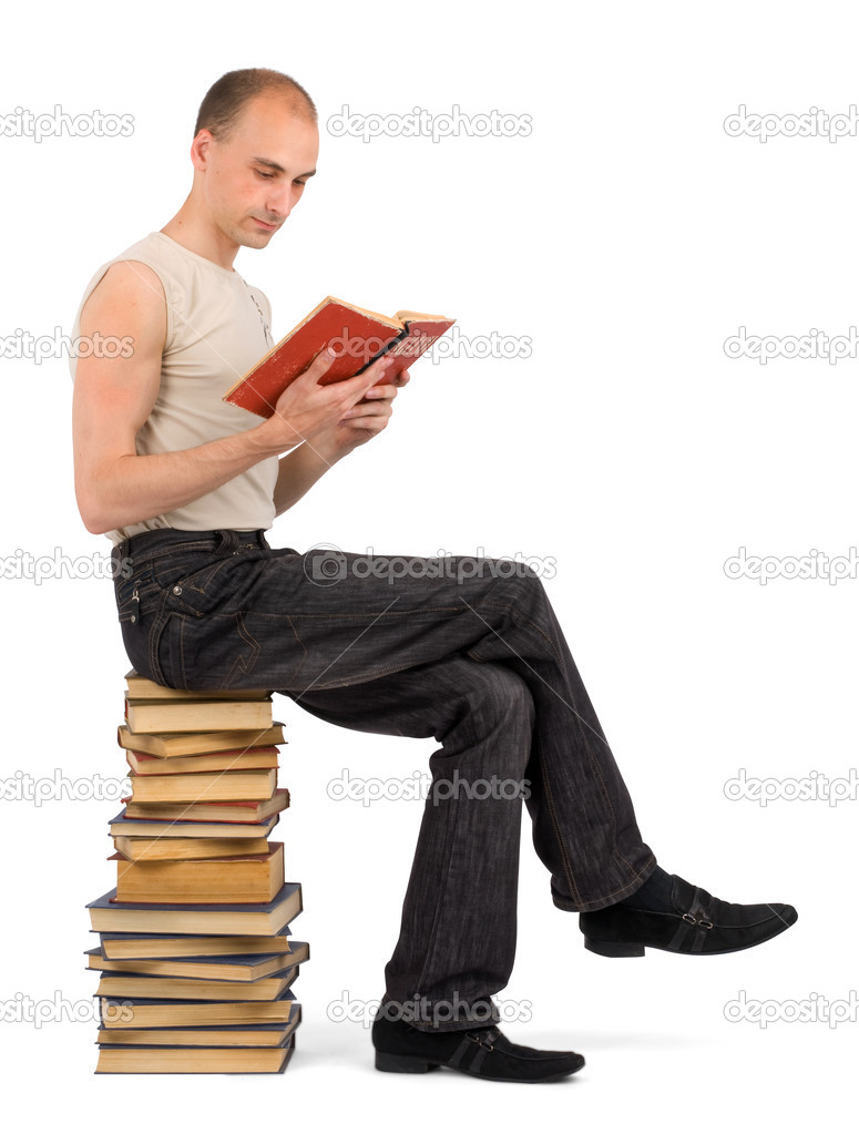 Man sitting on the heap of books and reading one of them — Stock Photo #1060364