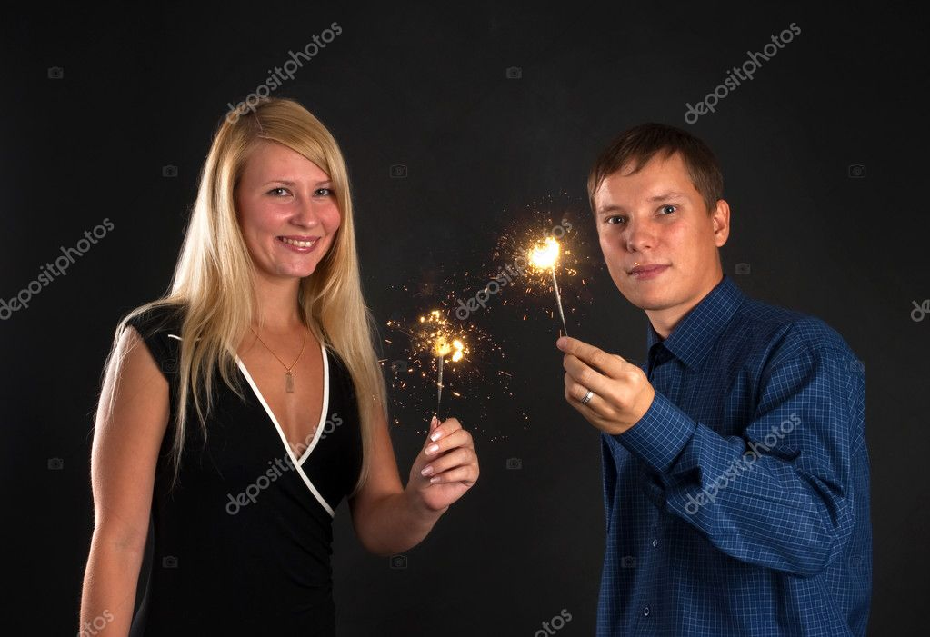 Young couple with Bengal fire in the dark — Stock Photo #1628641