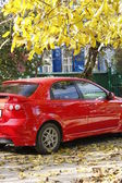 Red car in autumn park — Stock Photo