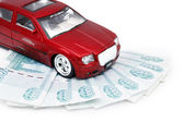 Red Car Miniature on money — Stock Photo