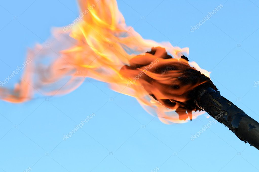 Closeup of flaming torch on blue background with copy space — Stock Photo #1085795
