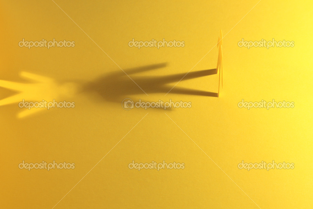 Paper man standing against his two shadows on yellow background — Stock Photo #1130258
