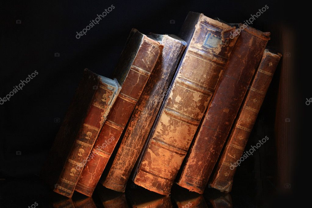 Old books in a row isolated on dark background — Stock Photo #1174884