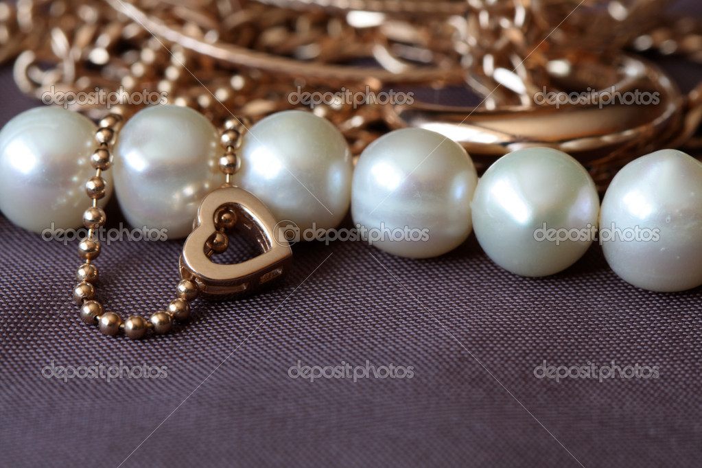 Closeup of various gold and pearl jewelry on brown textiles background  Stock Photo #1939226